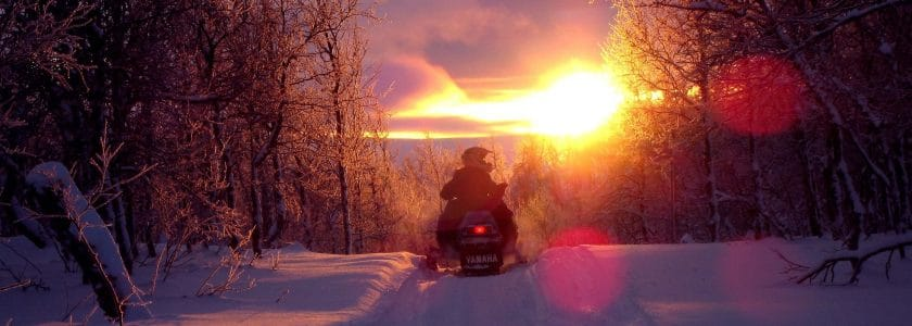 man snowmobiling in Morzine at dusk