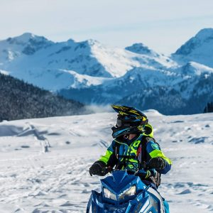 man snowmobiling in Morzine whilst looking at the mountainous view
