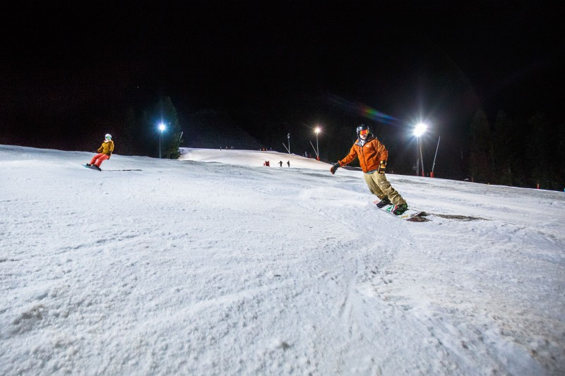 man snowboards down piste whilst night skiing in Morzine