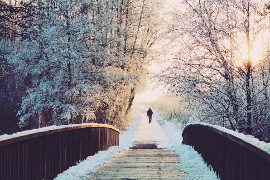 man walks along bridge whilst snowshoeing along the dereche in Morzine