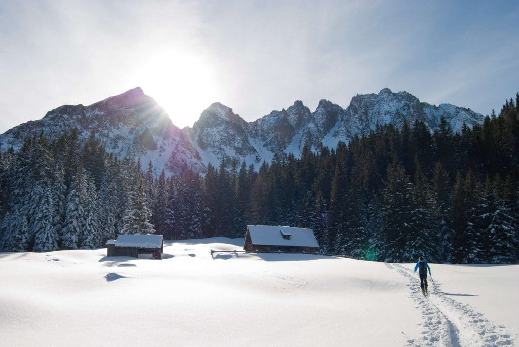 man snowshoeing in Morzine through snowy mountain hamlet