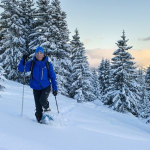 woman snowshoeing on Mont Chery through forest