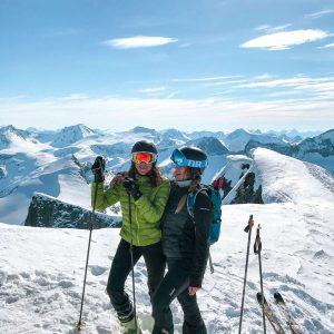 two women pose on snowy mountain